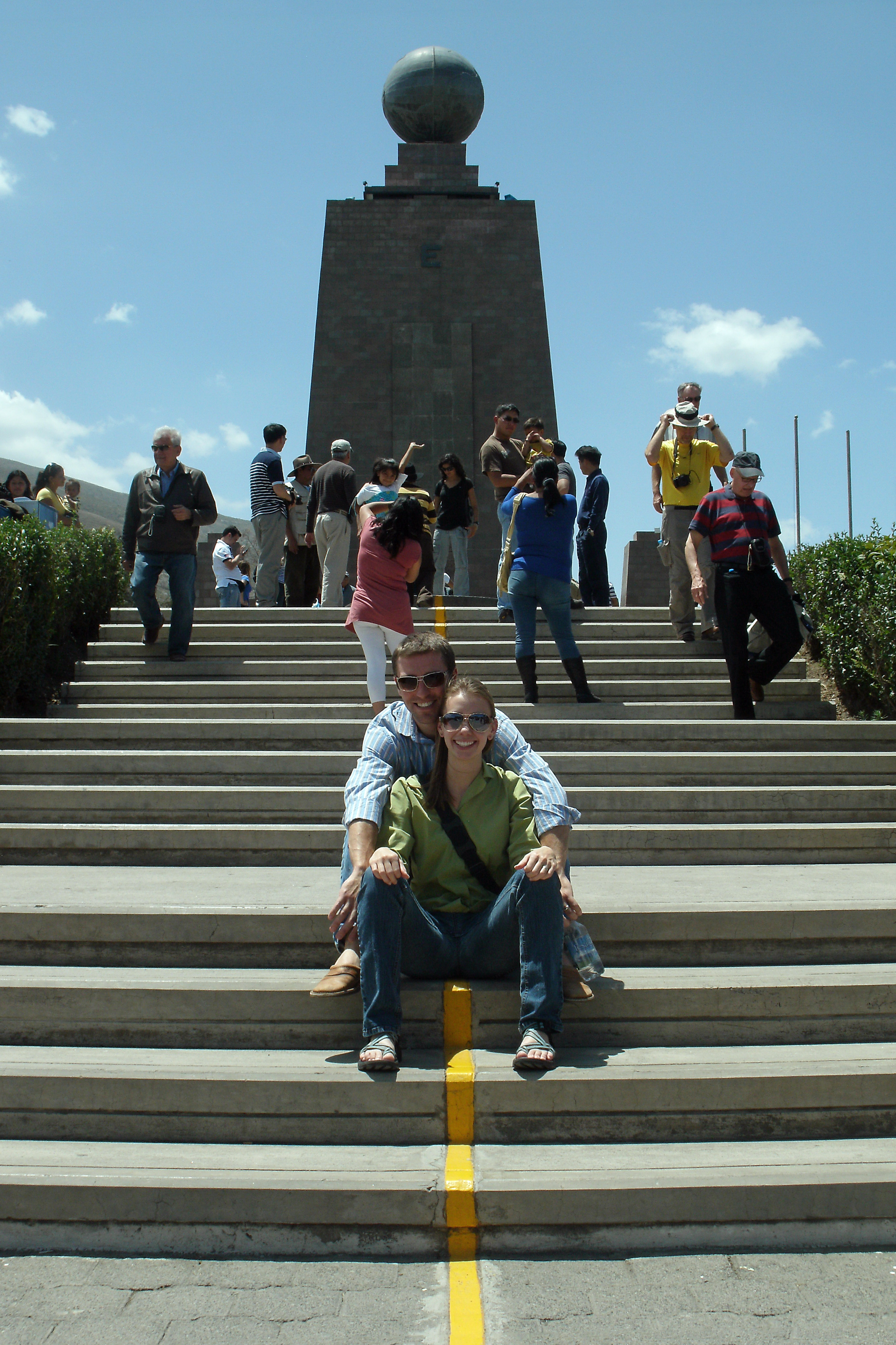 Couple Sitting on Equator at Middle of the World Monument in Ecuador